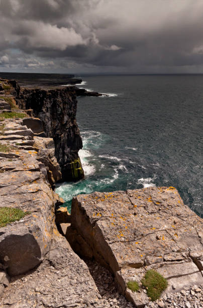 View east, southeast from the Cliff Edge of the Ancient fort wall of Dun Aonghasa (Dun Aengus), Inishmore, Aran Islands, County Galway, Ireland Breaking waves below the dramatic cliffs of the ancient fort Dun Aonghasa (Dun Aengus), in the distance the karst landscape of Inishmore with clouds of an approaching storm over Galway Bay.  Aran Islands, County Galway, Ireland. michael stephen wills aran stock pictures, royalty-free photos & images
