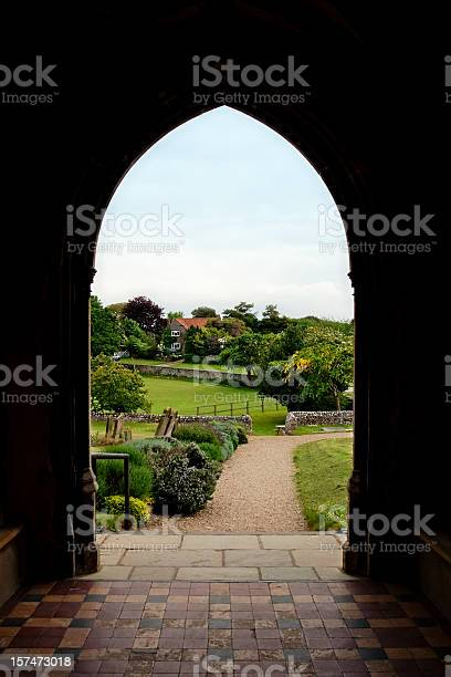 The view from a church door over the graveyard and nearby countryside. St Margaret of Antioch church, Cley next the Sea, Norfolk.
