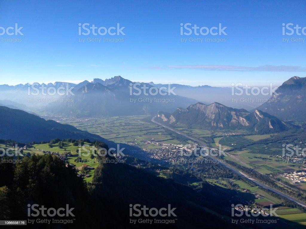 Blick von einem hohen alpinen Berggipfel in der Schweiz mit einem tollen Blick auf die Täler und Dörfer unten und dunstigen Berge hinter – Foto
