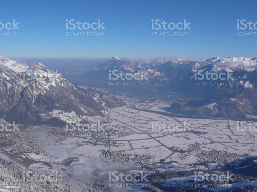 Blick von einem hohen alpinen Berggipfel in der Schweiz mit einem tollen Blick auf die Täler und Dörfer und Berge hinter all der wunderbaren weißen Winterschnee bedeckt – Foto