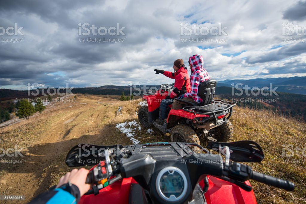 view from a quad bike couple sitting on atv man showing something