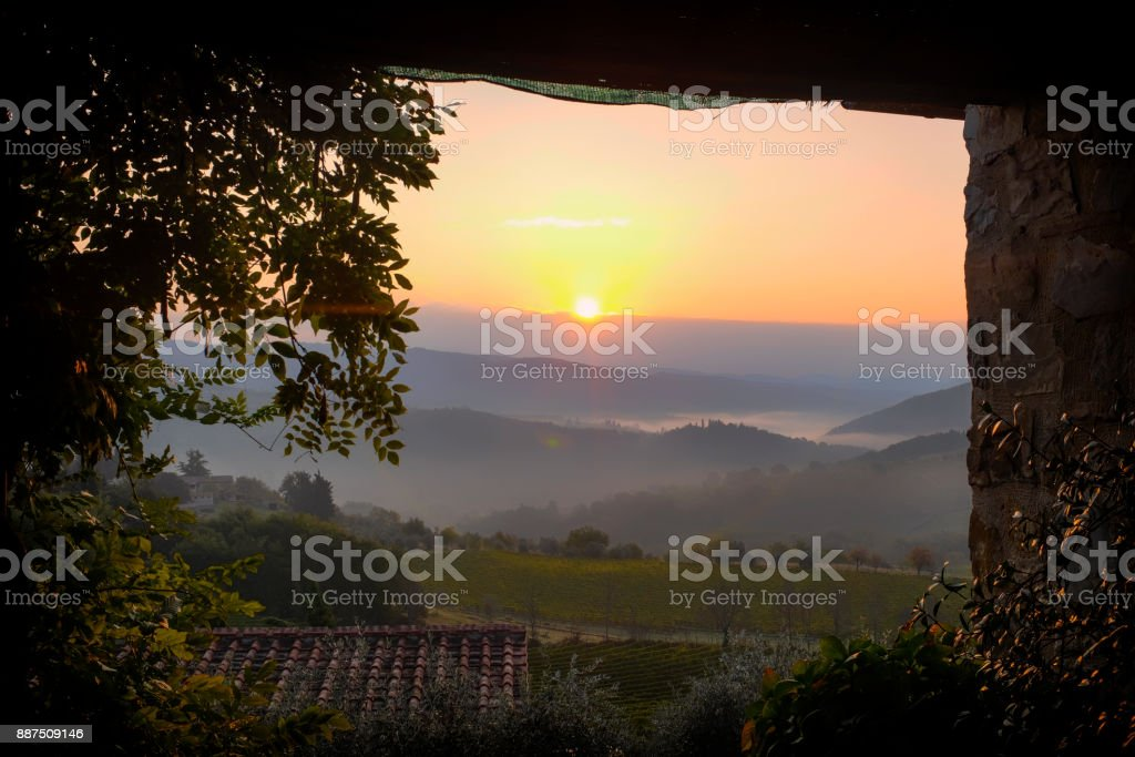 View from a terrace to a sunrise over foggy hills in the vineyards in Tuscany in Italy stock photo