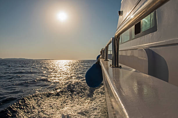 View from a yacht travelling at sunrise stock photo