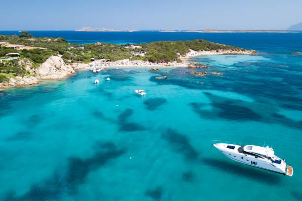 vista desde arriba, foto aérea de un barco flotando en el mar mediterráneo de color turquesa y transparente. costa esmeralda (costa esmeralda) en cerdeña, italia. - yacht fotografías e imágenes de stock
