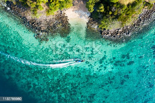 View from above, aerial view of a traditional long-tail boat sailing near a stunning barrier reef with a beautiful small beach bathed by a transparent and turquoise sea. Phi Phi Island, Thailand.