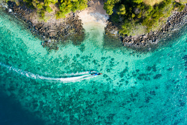 view from above, aerial view of a traditional long-tail boat sailing near a stunning barrier reef with a beautiful small beach bathed by a transparent and turquoise sea. phi phi island, thailand. - phuket stock photos and pictures