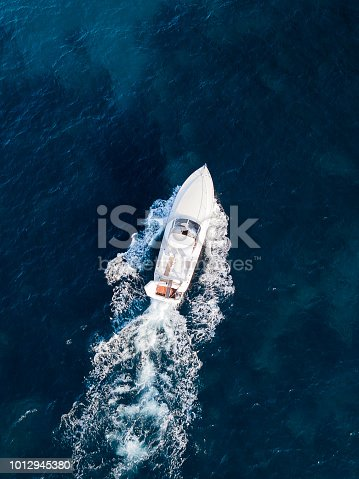 View from above, aerial view of a yacht sailing on an emerald and transparent Mediterranean sea. Emerald coast (Costa Smeralda), Sardinia, Italy.