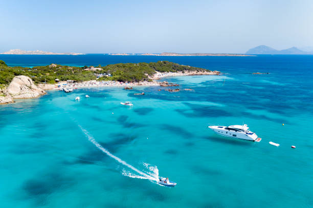 view from above, aerial view of an emerald and transparent mediterranean sea with a white beach and some boats and yachts. costa smeralda, sardinia, italy. - sardegna foto e immagini stock