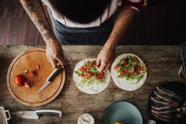 blick von oben auf koch macht veggie wraps - essen tattoos stock-fotos und bilder