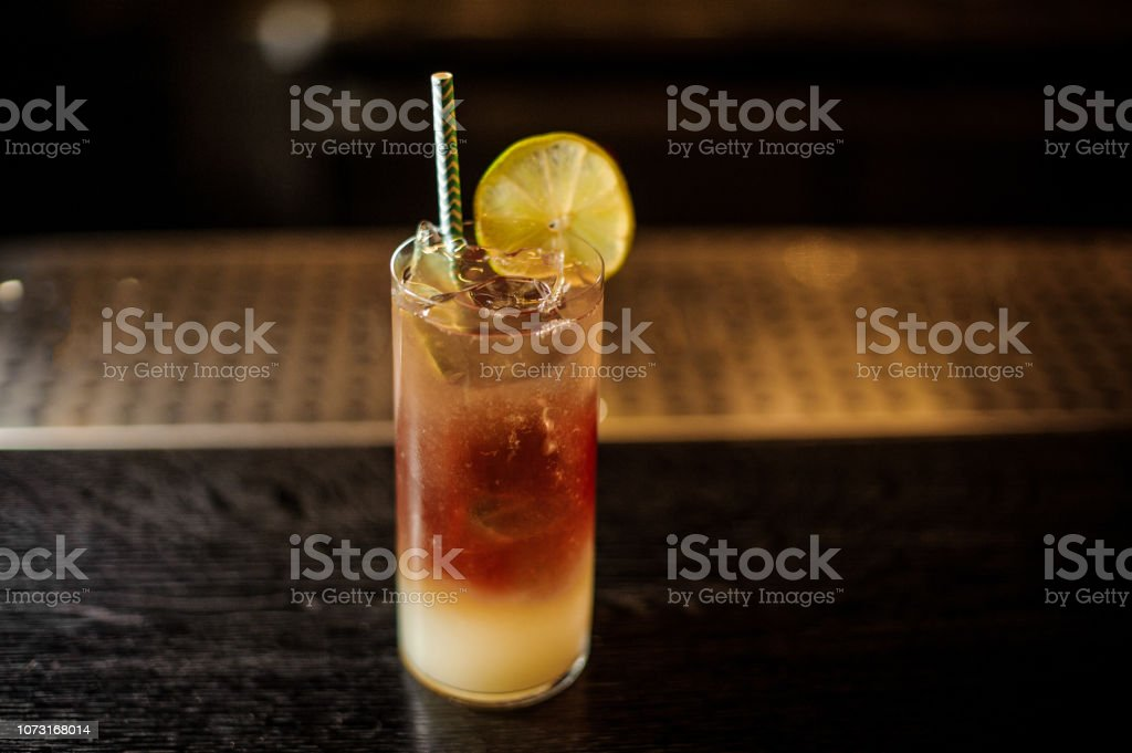 View from above Dark Stormy cocktail decorated with lime slice on the bar counter stock photo