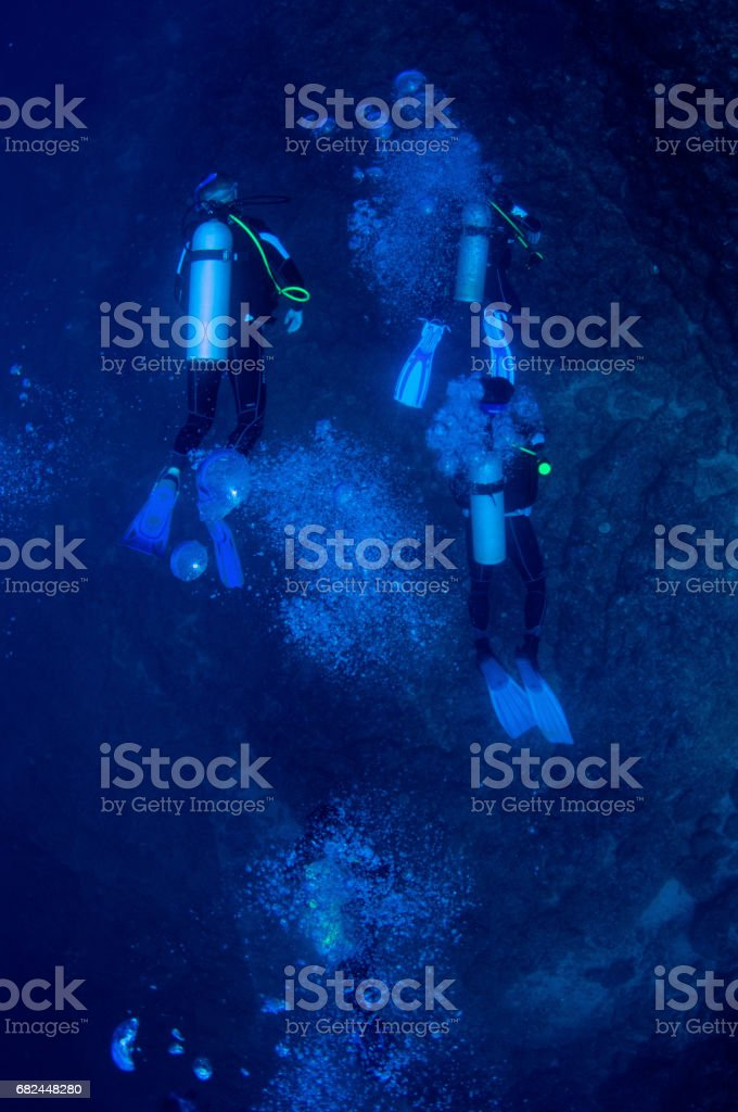 view from above multiple scuba divers with bubbles very blue and sandy and rocky bottom royalty-free stock photo