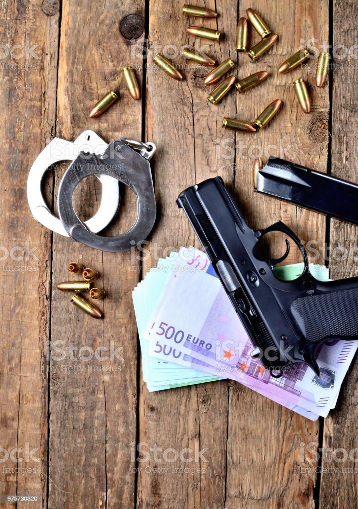Blick von oben auf 9mm Pistole Gun - Pistole, Handschellen, Spezialeinheiten der Polizei hohl-Punkt expandierenden Kugeln, Euro-Banknoten und -Magazin auf alten Holztisch - Lizenzfrei Abstrakt Stock-Foto