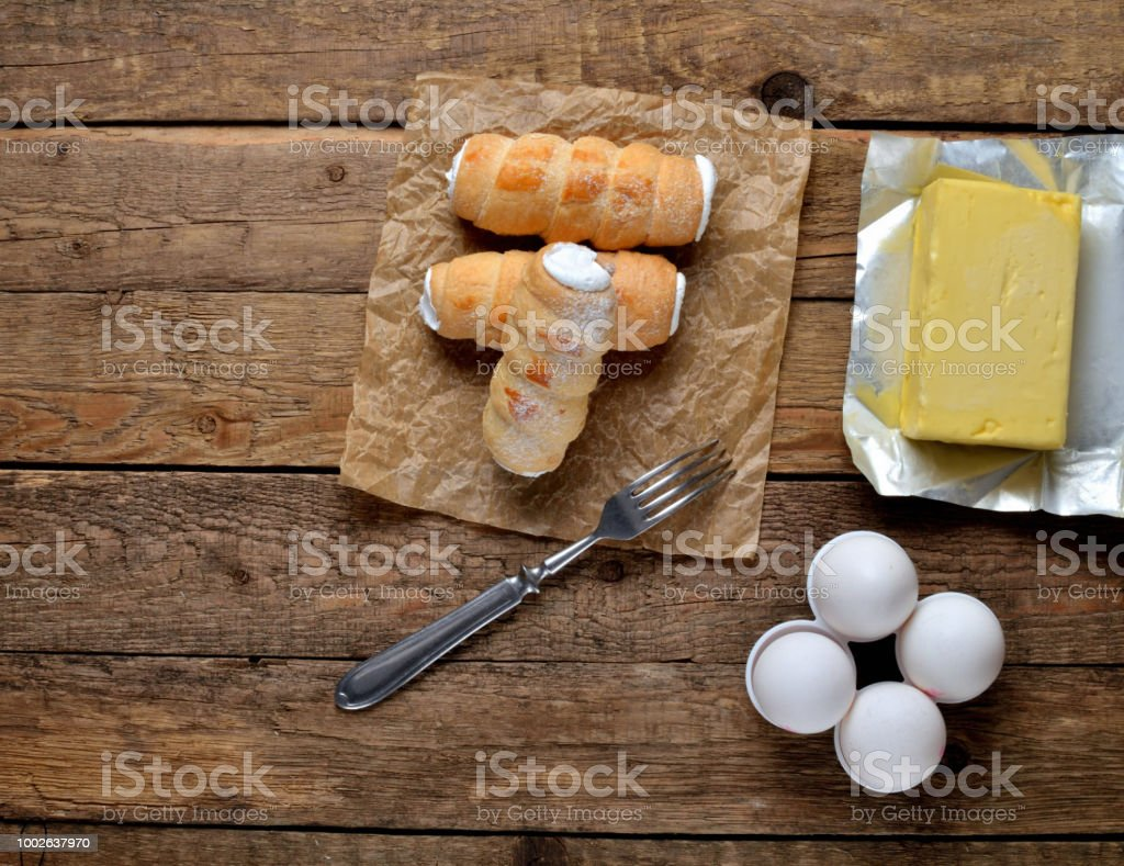 View from above of custard tube of pastry filled with cream - dessert cake - traditional czech sweet on baking paper, butter, eggs and fork on wooden table stock photo