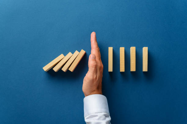 View from above of male hand interfering collapsing dominos View from above of male hand interfering collapsing dominos in a conceptual image of business crisis management. Over navy blue background. salvation stock pictures, royalty-free photos & images
