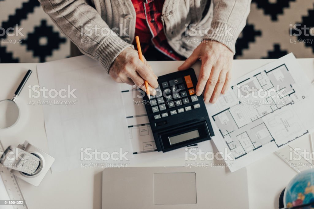 View from above of Older man using calculator at home office stock photo