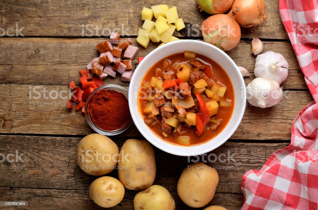 View from above of potato and sausage goulash, pepper, onion and garlic on wooden table and red dish-cloth stock photo