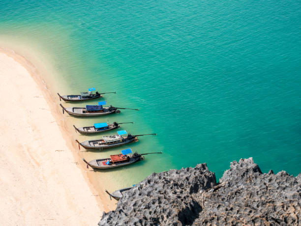 View from above of small wooden long tail boats on shore of a empty white sand beach and turquoise sea. Lots of room and space for copy text. Small rock in foreground. Thailand. stock photo