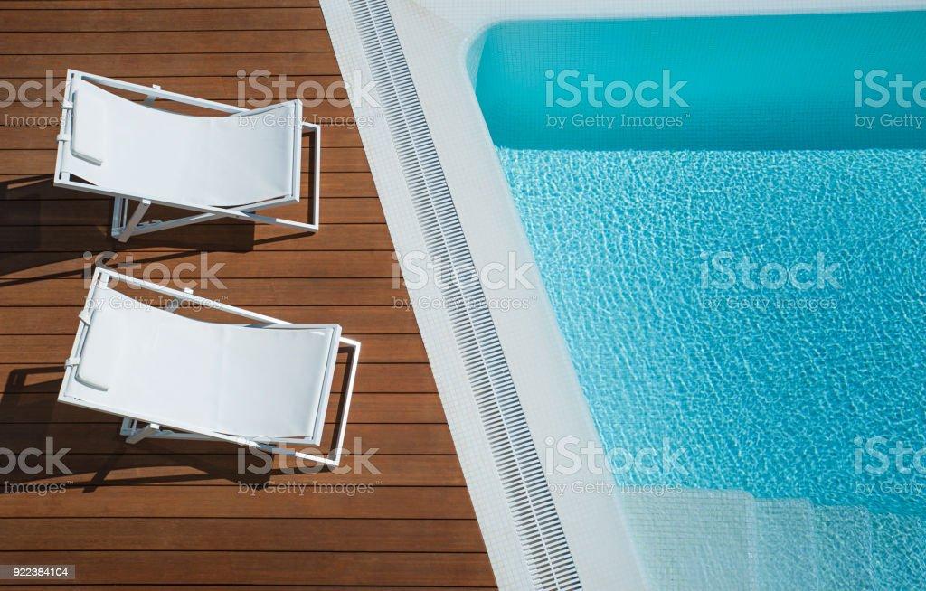 Vista desde arriba de dos sillas de salón de chaise lienzo en blanco colocados en una terraza de madera de color marrón en el exterior por una piscina color turquesa - foto de stock