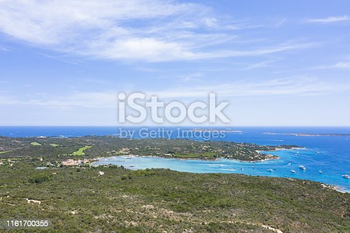 1066331604istockphoto View from above, stunning aerial view of a beautiful green coast bathed by a turquoise sea with some boats and yachts. Costa Smeralda (Emerald Coast) Sardinia, Italy. 1161700355