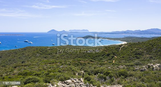 1066331604istockphoto View from above, stunning aerial view of a beautiful green coast bathed by a turquoise sea with some boats and yachts. Costa Smeralda (Emerald Coast) Sardinia, Italy. 1161700389