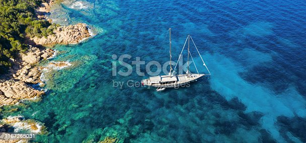 642777700 istock photo View from above, stunning aerial view of a luxury sailboat floating on a beautiful turquoise clear sea that bathes the green and rocky coasts of Sardinia. Emerald Coast (Costa Smeralda) Italy. 1167268031