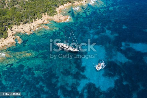 642777700 istock photo View from above, stunning aerial view of a luxury sailboat floating on a beautiful turquoise clear sea that bathes the green and rocky coasts of Sardinia. Emerald Coast (Costa Smeralda) Italy. 1167268044