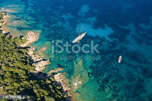 642777700 istock photo View from above, stunning aerial view of a luxury sailboat floating on a beautiful turquoise clear sea that bathes the green and rocky coasts of Sardinia. Emerald Coast (Costa Smeralda) Italy. 1167268090