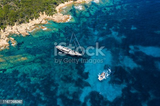 642777700 istock photo View from above, stunning aerial view of a luxury sailboat floating on a beautiful turquoise clear sea that bathes the green and rocky coasts of Sardinia. Emerald Coast (Costa Smeralda) Italy. 1167268092
