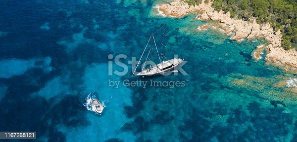 642777700 istock photo View from above, stunning aerial view of a luxury sailboat floating on a beautiful turquoise clear sea that bathes the green and rocky coasts of Sardinia. Emerald Coast (Costa Smeralda) Italy. 1167268121