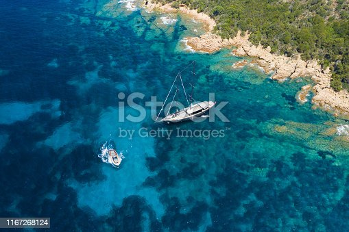 642777700 istock photo View from above, stunning aerial view of a luxury sailboat floating on a beautiful turquoise clear sea that bathes the green and rocky coasts of Sardinia. Emerald Coast (Costa Smeralda) Italy. 1167268124