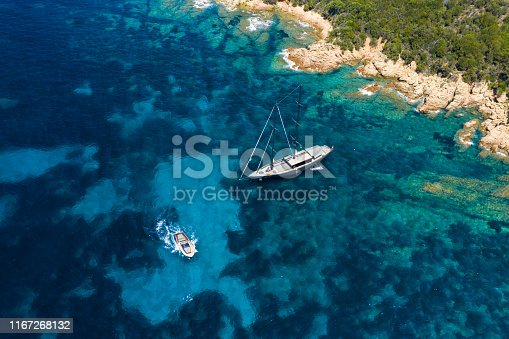 642777700 istock photo View from above, stunning aerial view of a luxury sailboat floating on a beautiful turquoise clear sea that bathes the green and rocky coasts of Sardinia. Emerald Coast (Costa Smeralda) Italy. 1167268132