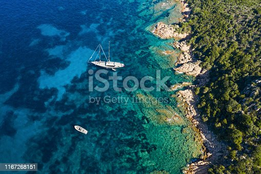 642777700 istock photo View from above, stunning aerial view of a luxury sailboat floating on a beautiful turquoise clear sea that bathes the green and rocky coasts of Sardinia. Emerald Coast (Costa Smeralda) Italy. 1167268151