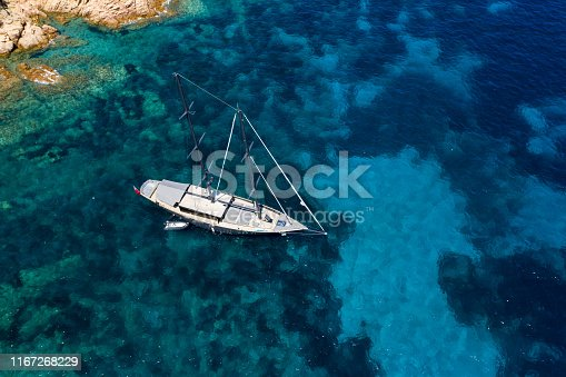 642777700 istock photo View from above, stunning aerial view of a luxury sailboat floating on a beautiful turquoise clear sea that bathes the green and rocky coasts of Sardinia. Emerald Coast (Costa Smeralda) Italy. 1167268229