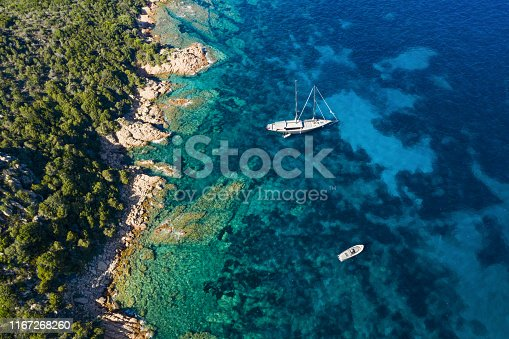642777700 istock photo View from above, stunning aerial view of a luxury sailboat floating on a beautiful turquoise clear sea that bathes the green and rocky coasts of Sardinia. Emerald Coast (Costa Smeralda) Italy. 1167268260