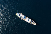 View from above, stunning aerial view of a luxury yacht sailing on a blue sea. Emerald Coast (Costa Smeralda) Sardinia, Italy.