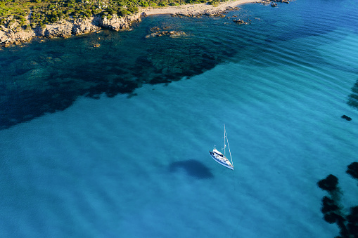 View from above, stunning aerial view of a sailing boat floating on a beautiful turquoise clear sea. Maddalena Archipelago National Park, Sardinia, Italy.