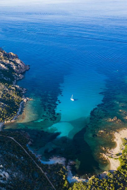 View from above, stunning aerial view of a sailing boat floating on a beautiful turquoise clear sea. Maddalena Archipelago National Park, Sardinia, Italy. View from above, stunning aerial view of a sailing boat floating on a beautiful turquoise clear sea. Maddalena Archipelago National Park, Sardinia, Italy. var stock pictures, royalty-free photos & images