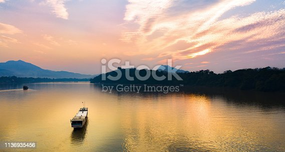 View from above, stunning aerial view of a tourists boat sailing along the Mekong river at sunset. Sunset Cruise is a slow-boat cruise along the Mekong river and is one of the most famous tourist attractions of Luang Prabamg, Laos.