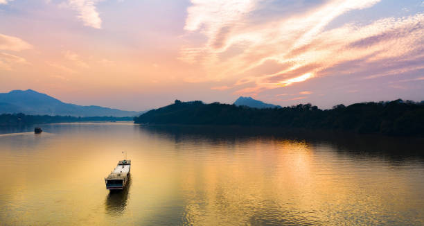 view from above, stunning aerial view of a tourists boat sailing along the mekong river at sunset. sunset cruise is a slow-boat cruise along the mekong river and is one of the most famous tourist attractions of luang prabamg, laos. - mekong river stock pictures, royalty-free photos & images