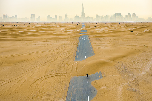 View from above, stunning aerial view of an unidentified person walking on a deserted road covered by sand dunes in the middle of the Dubai desert.  Dubai, United Arab Emirates.