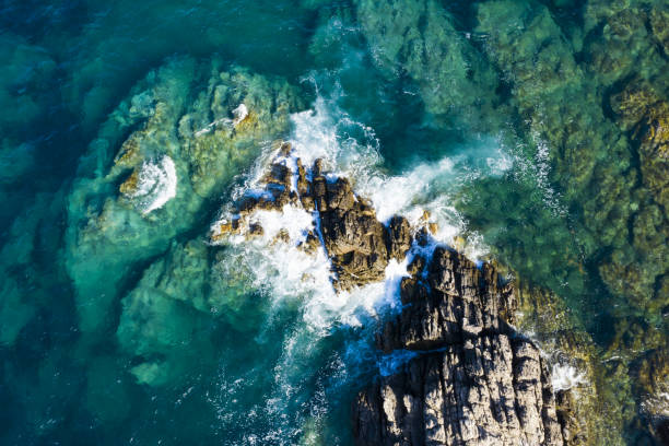 view from above, stunning aerial view of some waves crashing on a rocky coastline during a windy day in sardinia, italy. - rocky coastline stock pictures, royalty-free photos & images