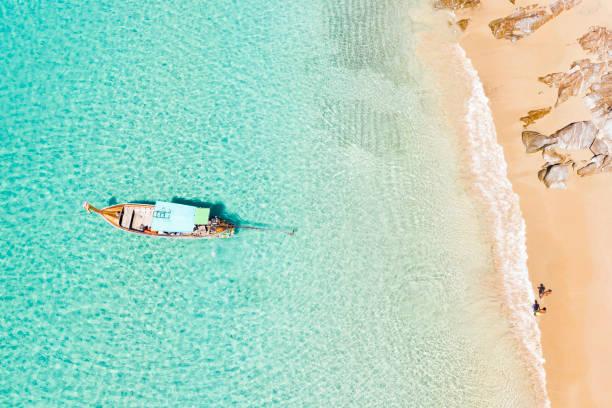 vista desde arriba, impresionante vista aérea de dos personas caminando en una hermosa playa tropical con arena blanca, agua cristalina turquesa y un barco de cola larga tradicional. banana beach, phuket, tailandia. - beach in thailand fotografías e imágenes de stock