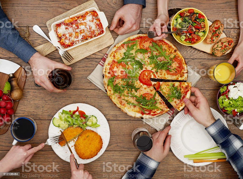 View from above the table of friends eating View from above the table of people eating Pizza Stock Photo