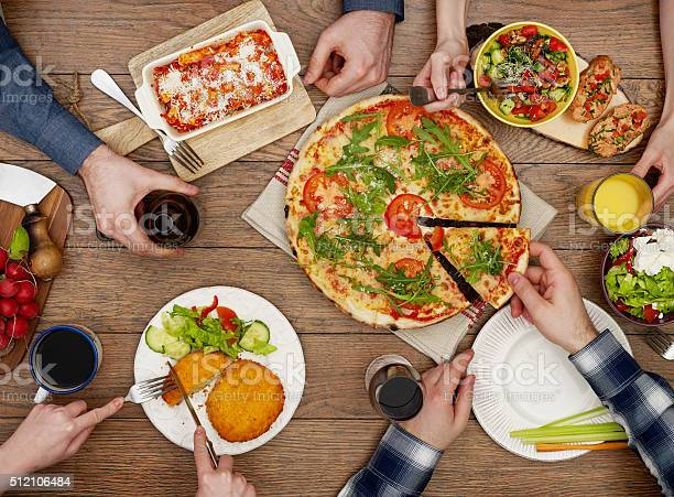 View From Above The Table Of Friends Eating Stock Photo - Download Image Now
