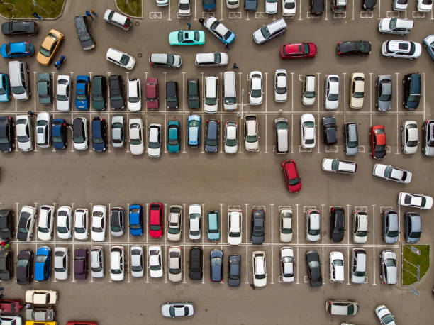 Blick von oben auf die Linien der geparkten Autos. Starker Verkehr auf dem Parkplatz. Auf der Suche nach Platz im belebten Fahrzeugpark. Kreuzfahrt zum Parken im Schlafsaal. Platzmangel für das Automobil. – Foto