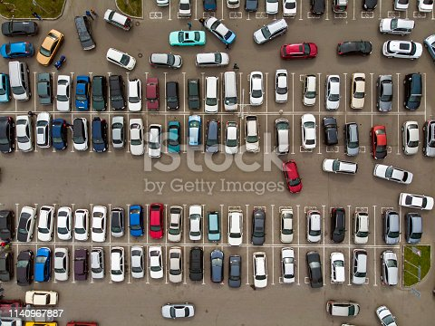 A view from above to the lines of parked cars. Heavy traffic in the parking lot. Searching for spaces in the busy car park. Cruising for parking in dormitory area. Difficulties of parking in the city.