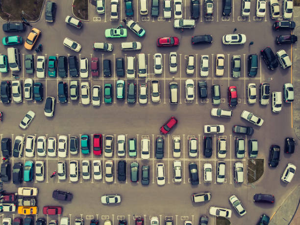 View from above to the process of car parking. Heavy traffic in parking lot. Searching for spaces in the car park. Leaving car in the stand. Cruising in a busy business center. Setup difficulties. stock photo