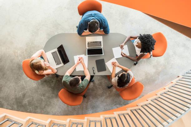 widok z góry na pięciu biznesmenów wokół stołu konferencyjnego - znad głowy zdjęcia i obrazy z banku zdjęć