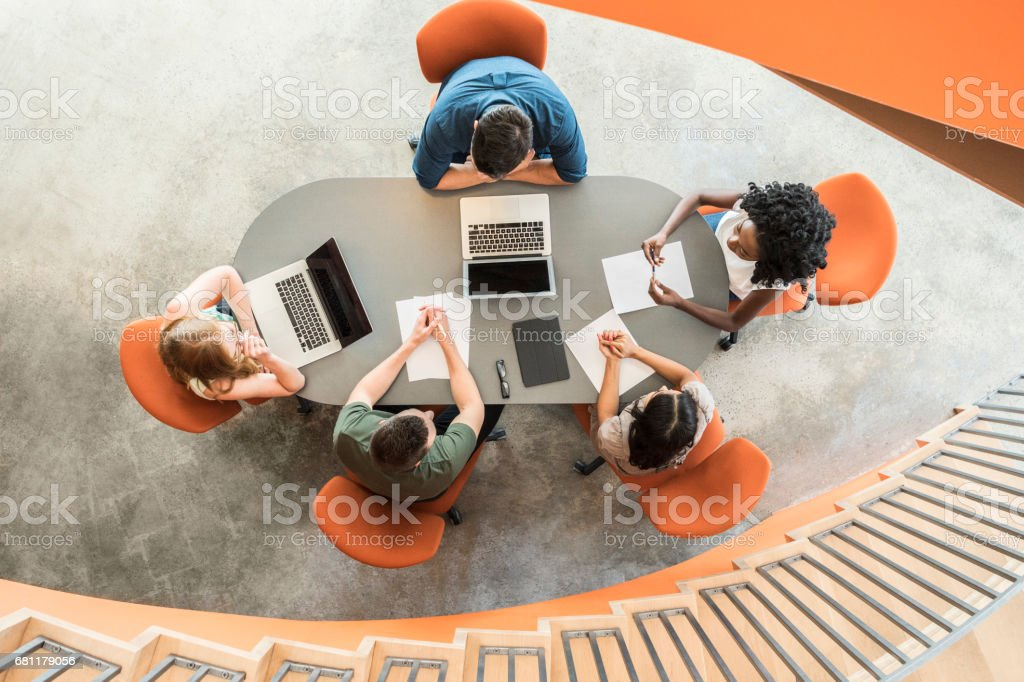 View from above towards five business people around meeting table stock photo