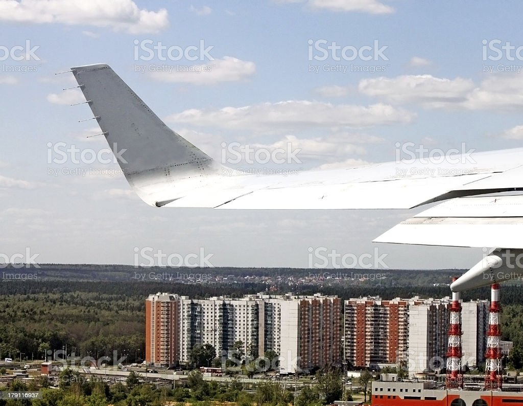 View from airplane of the wing and a city beneath royalty-free stock photo